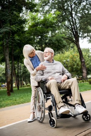 Photo for Nice senior woman with husband in wheelchair in park - Royalty Free Image