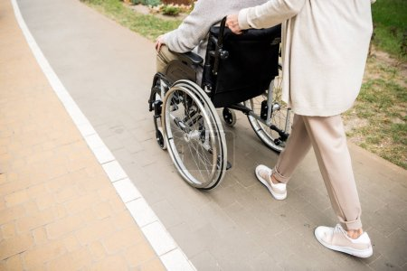 Photo for Cropped view of senior woman with husband in wheelchair - Royalty Free Image