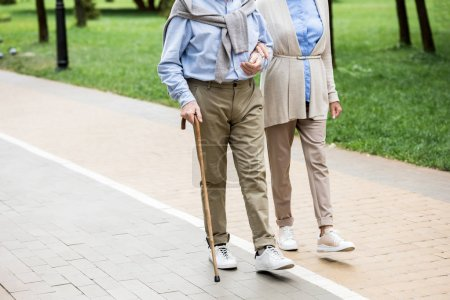 Photo for Cropped view of senior couple walking in park - Royalty Free Image