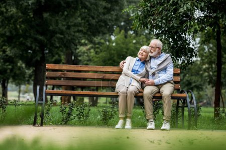 Photo for Smiling senior couple embracing and holding hands while resting on wooden bench in park - Royalty Free Image