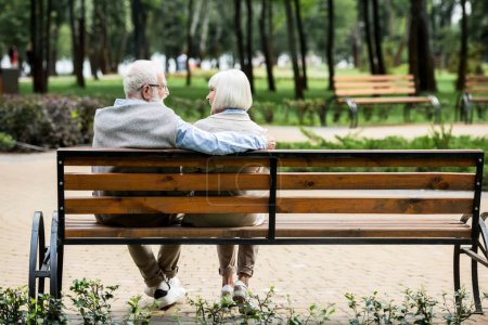 Photo for Senior couple sitting on wooden bench in park - Royalty Free Image