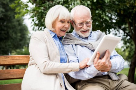 Photo for Happy smiling senior couple using digital tablet while sitting on bench in park - Royalty Free Image