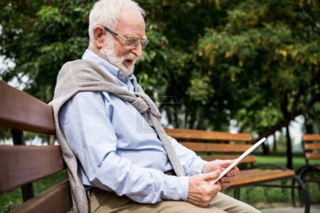 Photo for Selective focus of senior man using digital tablet while sitting on wooden bench in park - Royalty Free Image