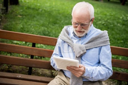 Photo for Smiling senior man using digital tablet while sitting on wooden bench - Royalty Free Image