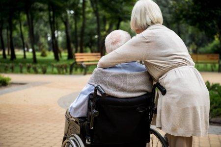 Photo pour Vue arrière du senior femme avec mari en fauteuil roulant dans le parc - image libre de droit