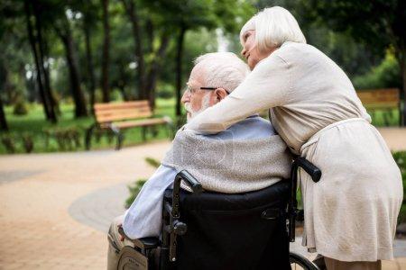 Seniorin mit Mann im Rollstuhl im Park