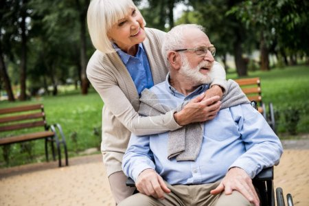 Photo for Happy senior woman with smiling husband in wheelchair in park - Royalty Free Image