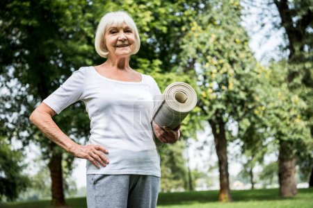 Photo for Happy senior woman with fitness mat holding hand on hip - Royalty Free Image