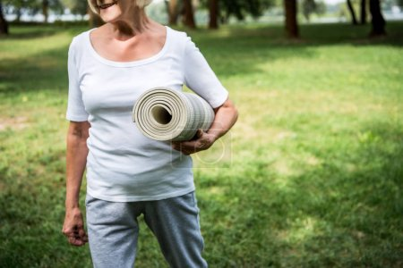 Photo for Partial view of senior woman holding fitness mat while walking in park - Royalty Free Image