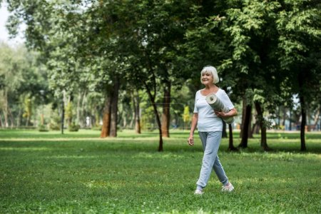 Photo for Smiling senior woman holding fitness mat while walking in park - Royalty Free Image