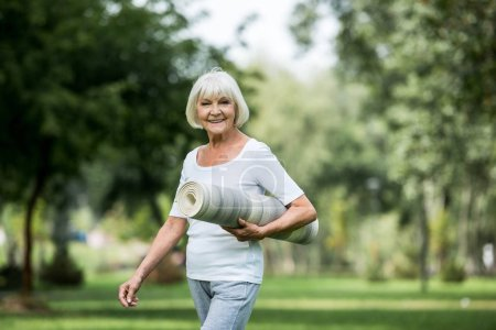 Photo for Happy senior woman with fitness mat walking in park - Royalty Free Image