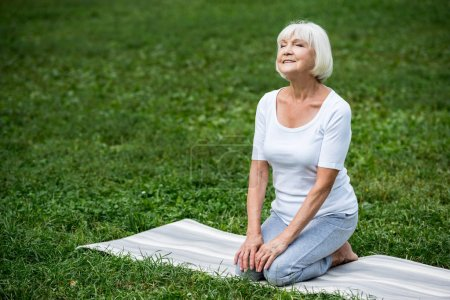 Photo for Happy senior woman sitting in meditation pose with hands on knees and closed eyes - Royalty Free Image