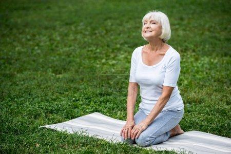 Photo pour Heureuse femme senior assis en posture de méditation avec les mains sur les genoux et les yeux fermés - image libre de droit