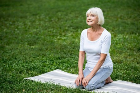 Photo for Smiling senior woman sitting on yoga mat in meditation pose with hands on knees - Royalty Free Image