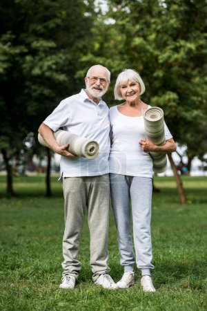 Photo for Happy senior couple hugging while standing with fitness mats in park - Royalty Free Image