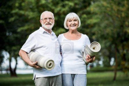 Photo pour Couple de personnes âgées tenue fitness tapis en se tenant debout dans le parc de sourire - image libre de droit