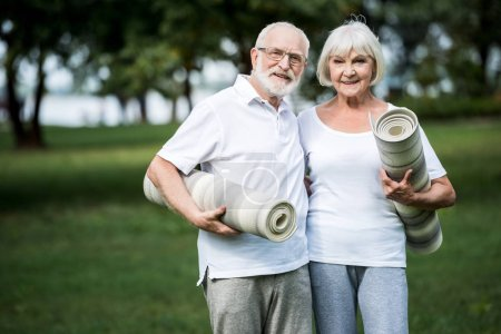 Photo for Smiling senior couple embracing while holding fitness mats - Royalty Free Image
