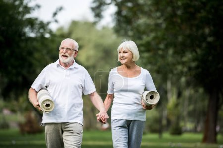 Photo for Smiling senior couple with fitness mats walking in park and holding hands - Royalty Free Image