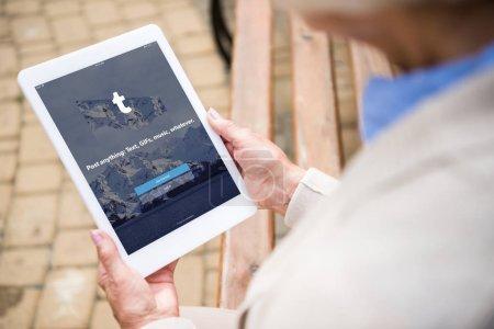 Photo pour Foyer sélectif de la femme âgée en utilisant une tablette numérique avec l'application tumblr à l'écran - image libre de droit