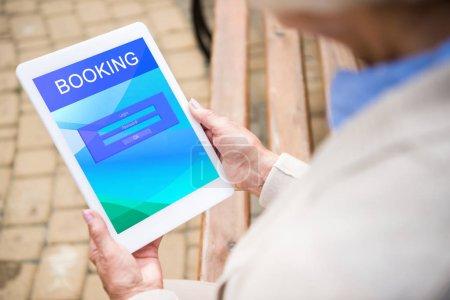 Photo pour Foyer sélectif de la femme âgée en utilisant un ordinateur portable numérique avec réservation à l'écran - image libre de droit