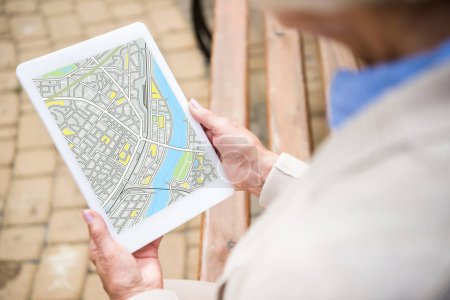 Photo for Selective focus of senior woman holding digital tablet with map on screen - Royalty Free Image