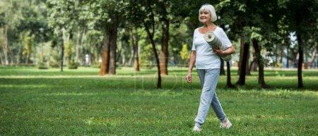 Photo pour Heureuse femme senior marche dans le parc et la tenue des tapis fitness - image libre de droit
