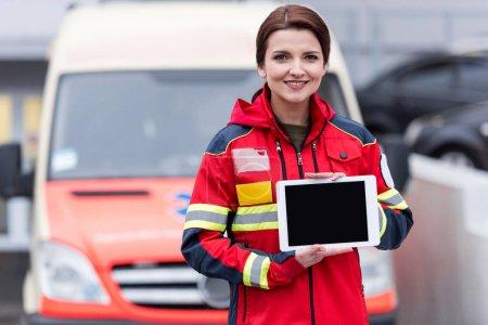 Photo pour Paramédic souriant en uniforme rouge, tenant une tablette numérique avec écran blanc - image libre de droit