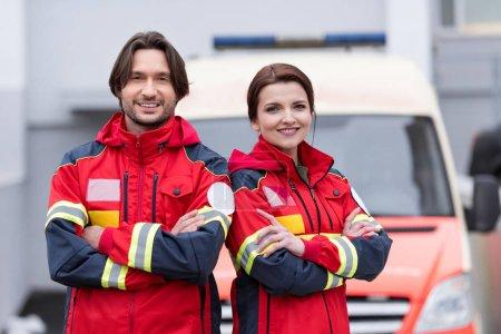 Photo pour Souriant personnel paramédical en uniforme debout avec les bras croisés - image libre de droit