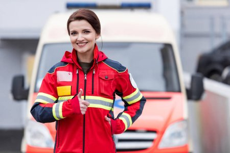 Photo pour Charmante femme paramédic dans Affichage uniforme rouge pouce vers le haut - image libre de droit