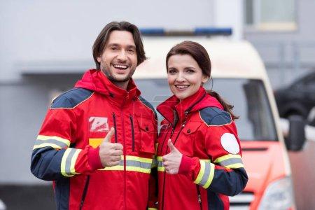 Photo pour Riant ambulanciers en rouge montrant uniforme thumbs up - image libre de droit