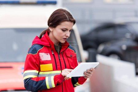 Photo pour Concentré de paramédic femelle en uniforme à l'aide de tablette numérique - image libre de droit
