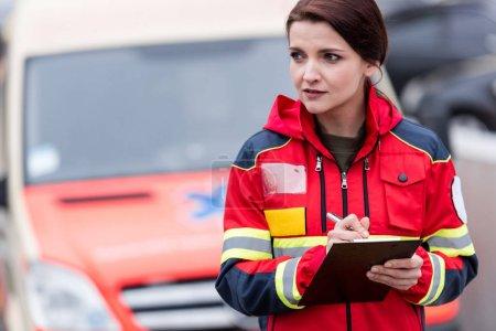 Photo pour Paramédic femme en uniforme rouge écrit dans le presse-papiers - image libre de droit