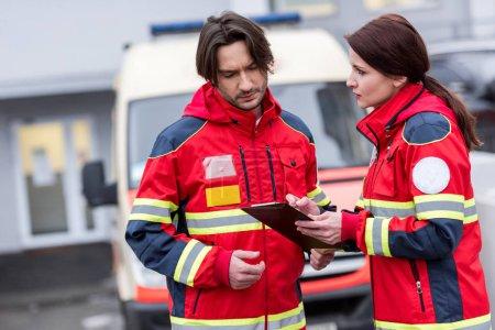 Photo pour Ambulanciers graves en uniforme rouge, lecture des notes dans le presse-papiers - image libre de droit