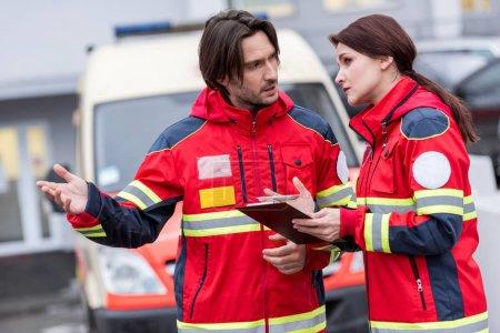 Photo pour Auxiliaires médicaux en rouge uniforme avec presse-papiers parlant dans rue - image libre de droit
