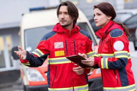 Photo pour Auxiliaires médicaux en rouge uniforme parlant et en regardant loin sur la rue - image libre de droit