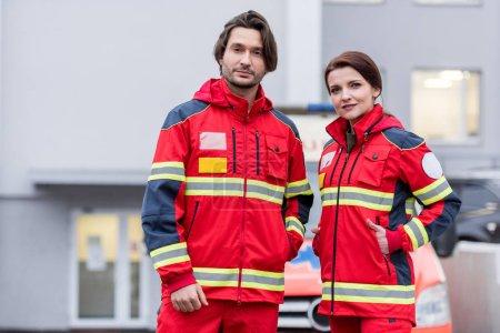 Photo pour Auxiliaires médicaux en uniforme rouge permanent sur la rue et de regarder la caméra - image libre de droit