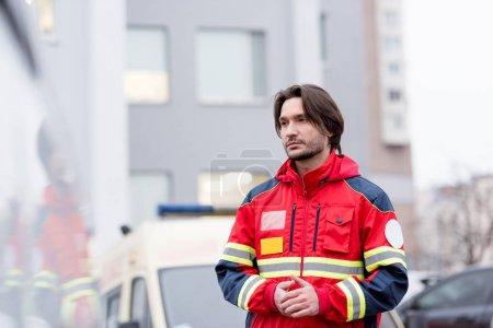 Photo pour Paramédic songeur en rouge uniforme debout sur la rue - image libre de droit