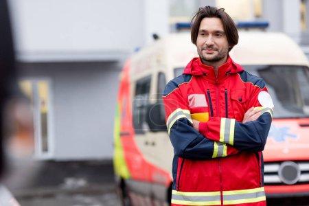 Photo pour Paramédic confiant en rouge uniforme debout sur la rue avec les bras croisés - image libre de droit