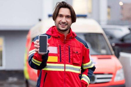 Photo pour Paramédic souriant en uniforme rouge tenant smartphone avec écran blanc - image libre de droit