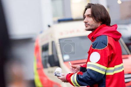 Photo pour Paramédic pensif avec presse-papiers en regardant loin sur la rue - image libre de droit