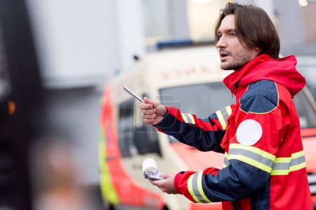 Photo pour Paramédic brune en uniforme rouge tenant le stylo et presse-papiers sur rue - image libre de droit