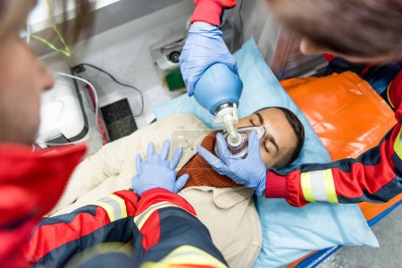 Photo pour Paramedics doing cardiopulmonary resuscitation in ambulance car - image libre de droit