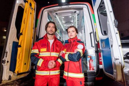 Photo pour Les ambulanciers en uniforme rouge debout devant la voiture d'ambulance - image libre de droit