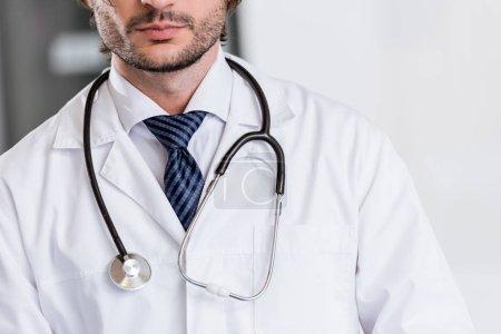 Photo pour Vue recadrée du médecin en manteau blanc avec stéthoscope - image libre de droit
