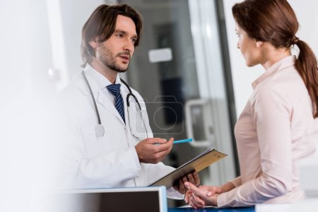 Photo for Doctor with clipboard talking to patient in clinic - Royalty Free Image