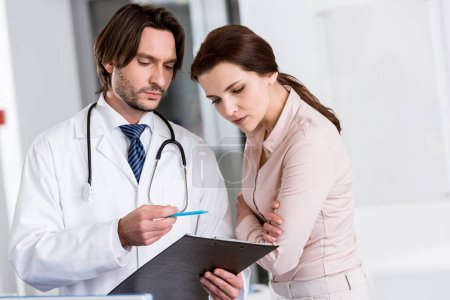 Photo for Doctor with stethoscope and patient looking at clipboard - Royalty Free Image