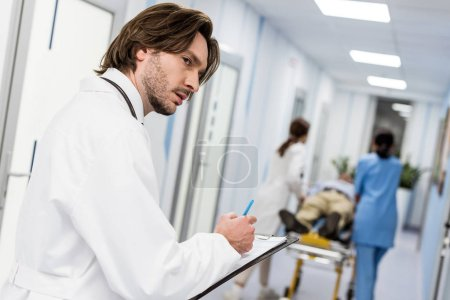 Photo for Serious young doctor in white coat writing notes in clipboard - Royalty Free Image
