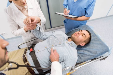 Photo for Cropped view of doctors and sick patient lying on gurney in clinic - Royalty Free Image