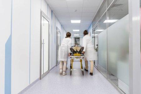 Foto de Grupo de médicos transportando pacientes en camilla - Imagen libre de derechos
