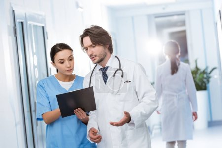 Photo for Nurse with clipboard showing notes to doctor - Royalty Free Image